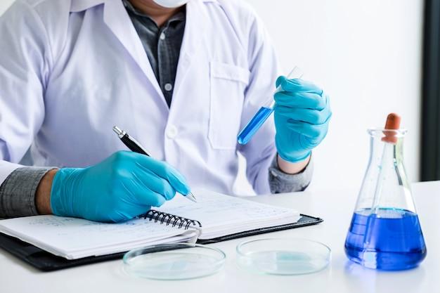 Químico analiza muestra en laboratorio con equipo y experimentos científicos.