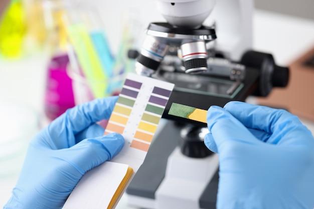 Químico científico sosteniendo la prueba de ph en sus manos determinación de primer plano del concepto de acidez