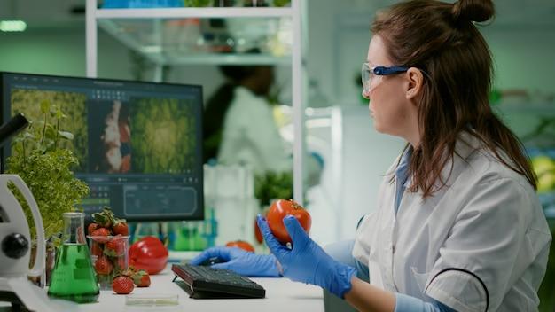 Químico farmacéutico examinando tomate para experimento de microbiología escribiendo información médica