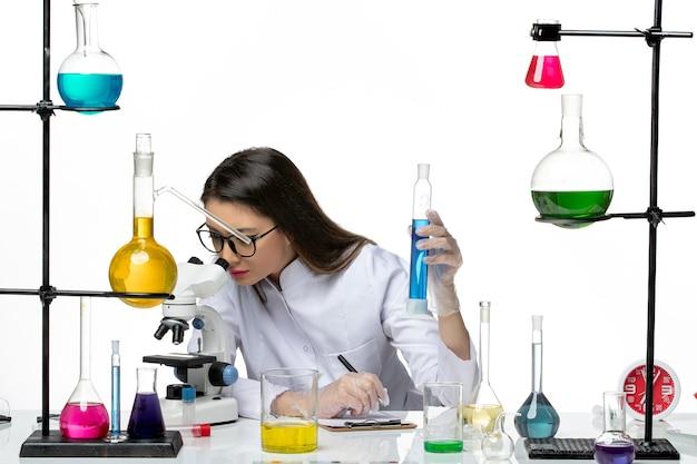 Químico femenino de vista frontal en traje médico blanco con matraz con solución usando microscopio sobre fondo blanco laboratorio de pandemia de virus de ciencia covid