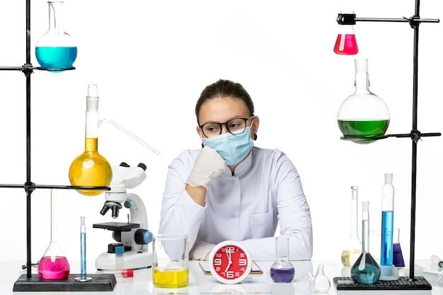 Químico femenino de vista frontal en traje médico con máscara sentado con soluciones y pensando en el laboratorio de química de virus de salpicaduras de fondo blanco covid-