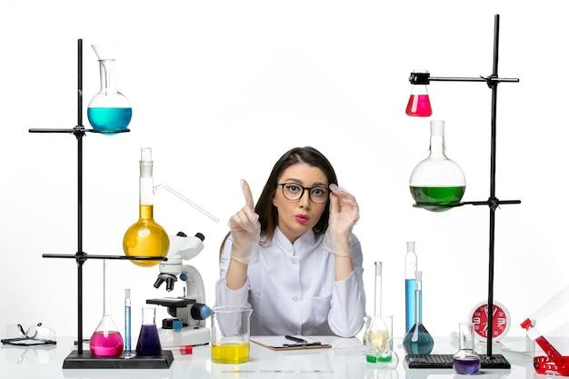 Químico femenino de vista frontal en traje médico sentado alrededor de la mesa con soluciones sobre fondo blanco ciencia pandemia covid virus de laboratorio