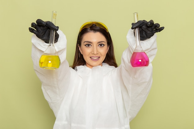 Químico femenino de vista frontal en traje de protección especial sosteniendo frascos con solución diferente en superficie verde