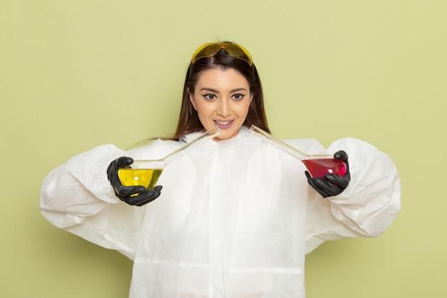 Químico femenino de vista frontal en traje de protección especial sosteniendo matraces con soluciones en superficie verde claro