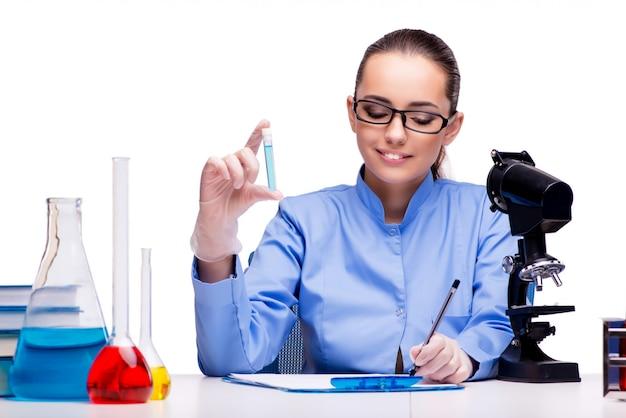 Químico de laboratorio trabajando con microscopio y tubos.