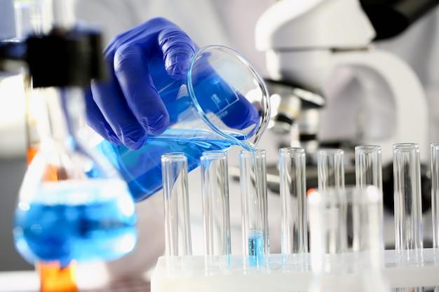 Un químico masculino sostiene un tubo de ensayo de vidrio en la mano.