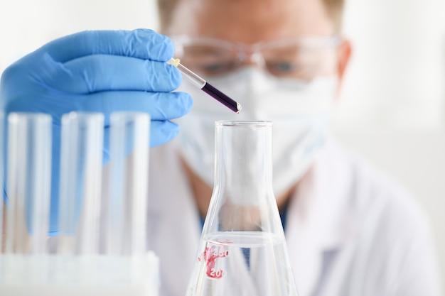 Un químico masculino sostiene un tubo de vidrio de ensayo en su mano, desborda una solución líquida de permanganato de potasio y realiza un análisis de las muestras de agua en versiones de reactivos que utilizan la fabricación química.