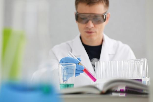 Un químico masculino sostiene un tubo de vidrio de ensayo en su mano, desborda una solución líquida de permanganato de potasio y realiza una reacción de análisis que toma varias versiones de reactivos utilizando fabricación química.