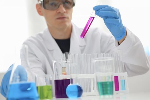 Un químico masculino sostiene un tubo de vidrio de ensayo