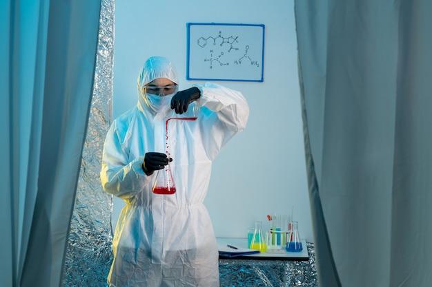 Un químico masculino en traje de protección y guantes trabajando con frascos de vidrio.