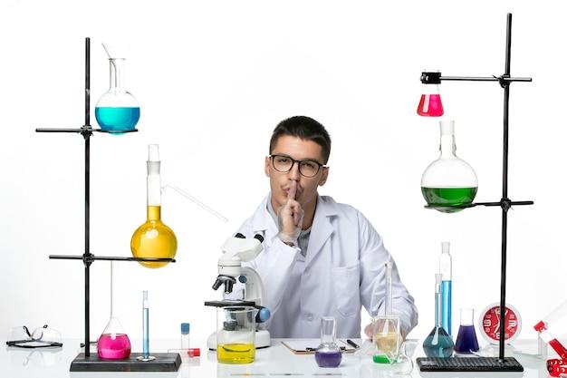 Químico masculino de vista frontal en traje médico blanco posando sobre fondo blanco laboratorio de virus covid- ciencia de la enfermedad