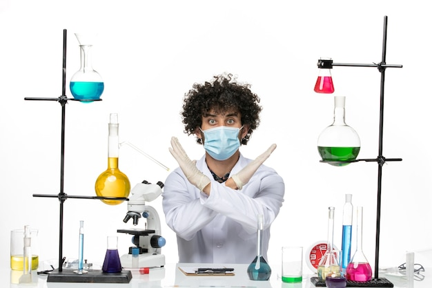 Químico masculino de vista frontal en traje médico y con máscara simplemente sentado con diferentes soluciones posando en el espacio en blanco