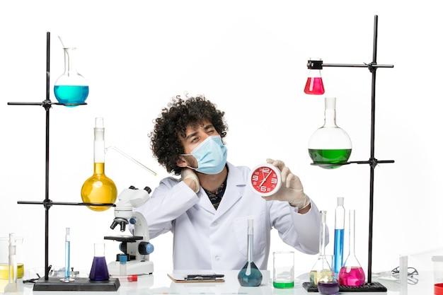 Químico masculino de vista frontal en traje médico y con máscara sosteniendo relojes rojos en el espacio en blanco