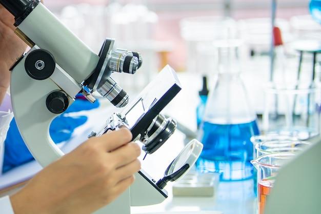 Químico profesional y biocientífico utilizando microscopio para investigar el muestreo de la nueva vacuna.
