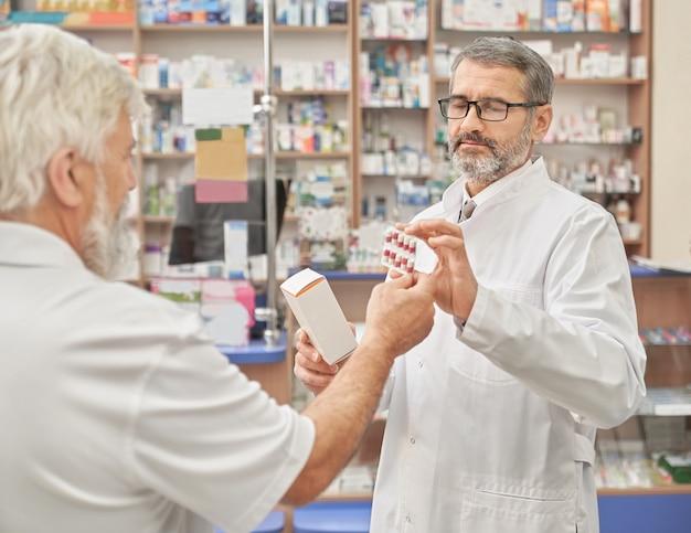 Químico que ofrece medicamentos al antiguo cliente en farmacia.