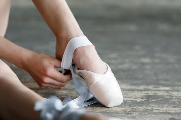 Quitándose las zapatillas de ballet después de ensayo o actuación