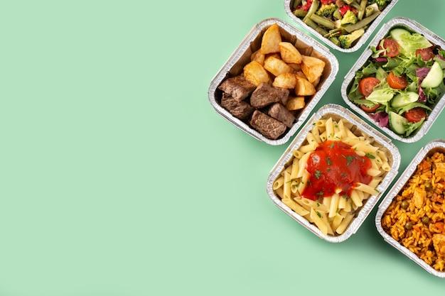 Quitar alimentos saludables en cajas de papel de aluminio sobre fondo verde