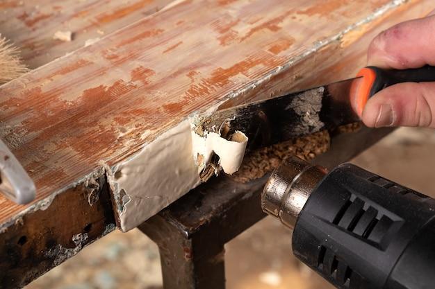 Quitar pintura vieja de puertas de madera viejas con una espátula y una pistola de calor para restaurar superficies de madera viejas