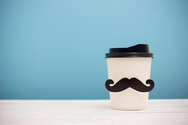 Quitar la taza de café con bigote inconformista en mesa de madera sobre fondo azul