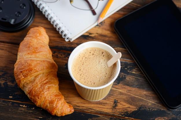 Quitar la taza de café con croissant en mesa de madera.