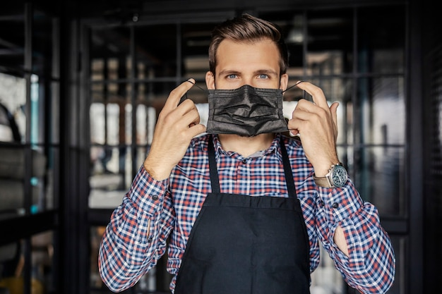 Quitarse o ponerse una mascarilla. un apuesto camarero de ojos hermosos lleva un reloj en la muñeca y se encuentra en la entrada del restaurante. servicios de restaurante en la época de la corona