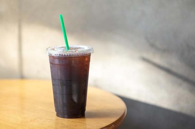 Quite la taza plástica de café negro helado americano en una mesa de madera con luz solar de la mañana