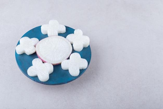 Rábano fresco en rodajas en un plato sobre una mesa de mármol.