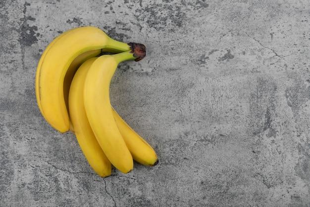 Racimo de plátano sano fresco maduro en la mesa de piedra.