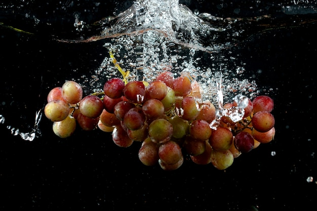 Racimo de uva salpicado en agua en negro