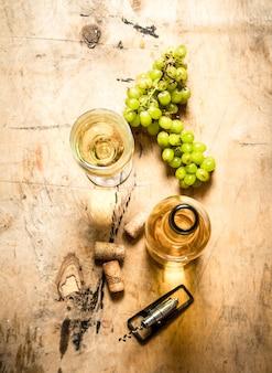 Racimo de uvas blancas con botella de vino, sacacorchos y tapones. sobre fondo de madera.
