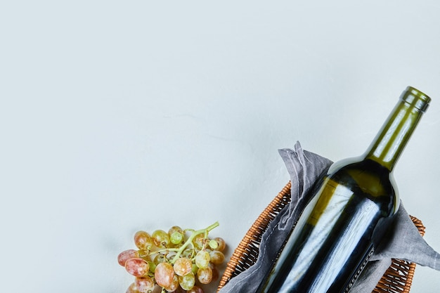 Racimo de uvas y una botella de vino sobre fondo gris. foto de alta calidad