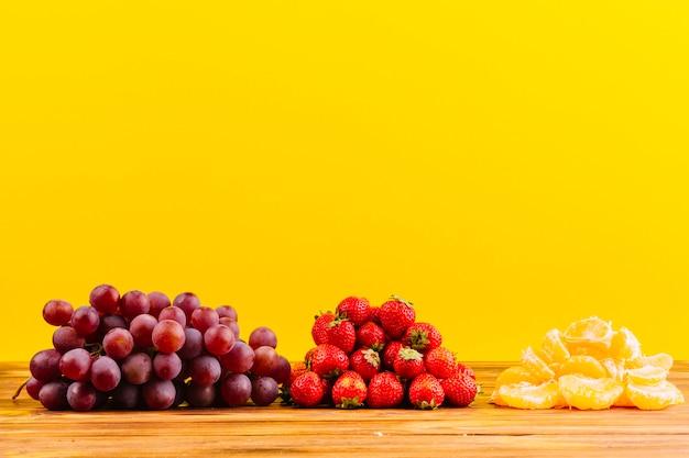 Racimo de uvas; fresas y rodaja de naranja en mesa de madera sobre fondo amarillo