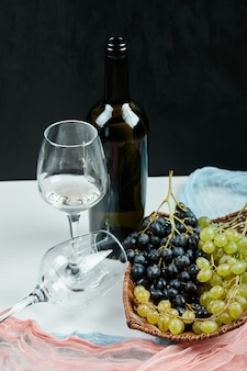 Un racimo de uvas mixtas en canasta y vasos de vino y botella con mantel rosa y azul. foto de alta calidad