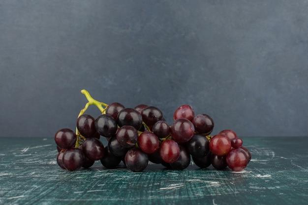 Un racimo de uvas negras sobre la mesa de mármol.