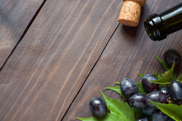 Racimo de uvas rojas y blancas, botella de vino y corcho sobre madera