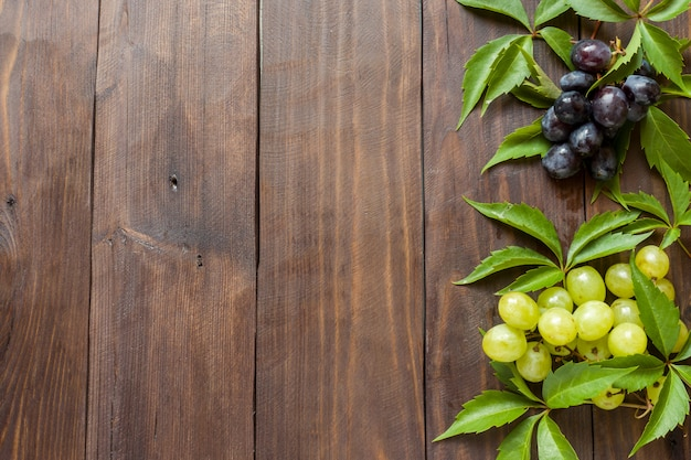 Racimo de uvas rojas y blancas sobre fondo de mesa de madera