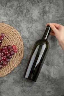 Racimo de uvas rojas y mano de mujer sosteniendo una botella de vino en la superficie de mármol.