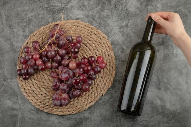 Racimo de uvas rojas y mano de niña sosteniendo una botella de vino en la superficie de mármol.