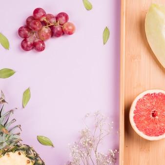 Racimo de uvas rojas; piña; toronja y melón con flores de gypsophila sobre fondo rosa