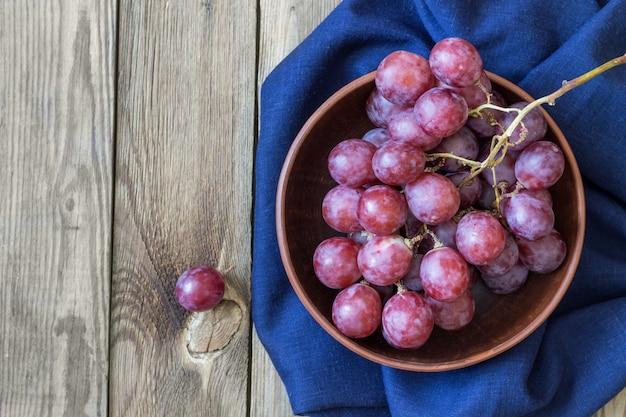 Racimo de uvas rojas en textiles azules en un recipiente, sobre una mesa de madera. copia espacio estilo rústico