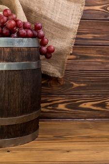 Racimo de uvas sobre barril de madera