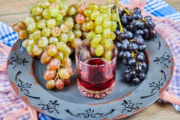 Racimo de uvas y un vaso de jugo en plato de cerámica con manteles