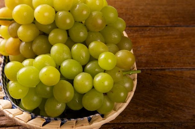 Racimo de uvas verdes en la cesta, frutos de otoño, un símbolo de abundancia sobre fondo de madera rústica con espacio de copia, vista superior, primer plano
