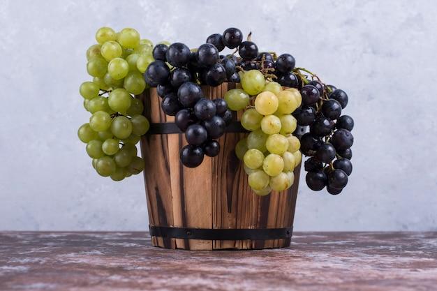 Un racimo de uvas verdes y rojas en un balde de madera