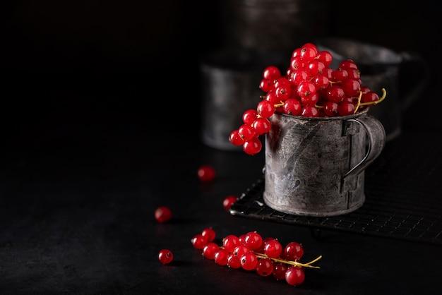 Racimos rojos maduros de grosellas en una taza de hierro sobre un fondo negro