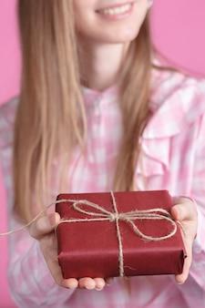 Rad giftbox en manos femeninas en rosa