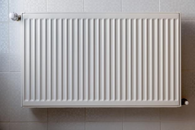 Radiador de calefacción de metal blanco montado en una pared en el interior de la habitación.
