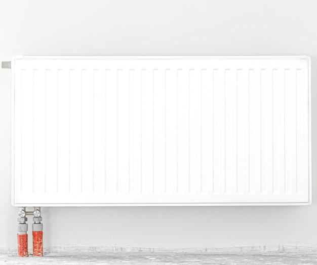 Radiador delante de una pared blanca. vista frontal.