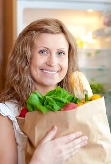 Radiante mujer sosteniendo una bolsa de supermercado