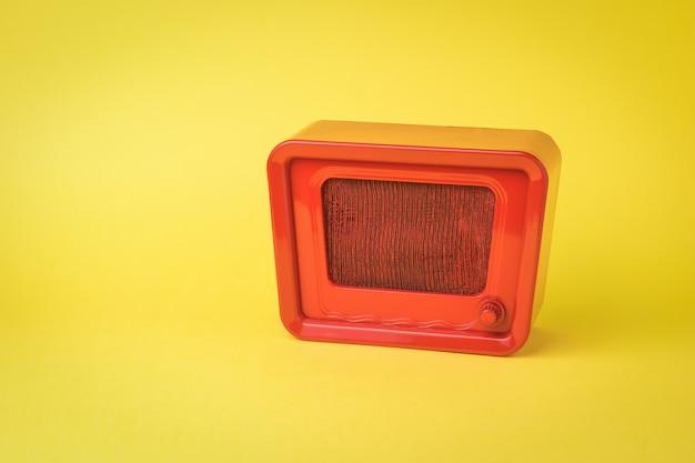 Radio retro rojo brillante sobre una superficie amarilla. diseño retro.